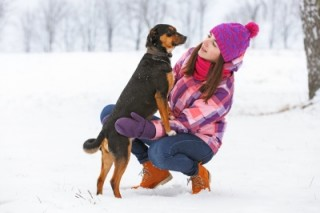 An image of a woman and her dog in the snow.
