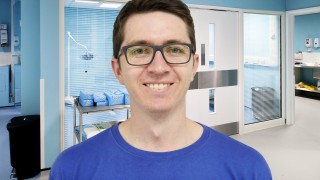 An image of John Burgess, a Vets Now Manchester intern, standing in a clinic for Vets Now article on Internships